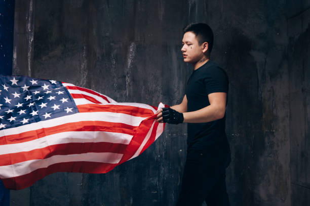 USA patriot with flying national flag and tattoo Young USA patriot with flying national flag. Strong man in black cloth with tattoo on dark studio background. Independence day, confidence, pride, fidelity to the nation, memorial day concept american flag tattoos for men stock pictures, royalty-free photos & images