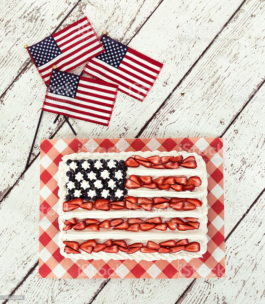 Patriotic American flag cake and decorative mini flags stock photo