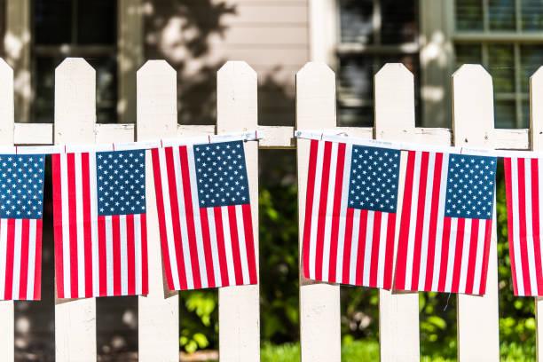 As bandeiras americanas patrióticas que penduram decorações na cerca de piquete branca em Aspen, Colorado perto da independência dia 4 de julho celebração - foto de acervo
