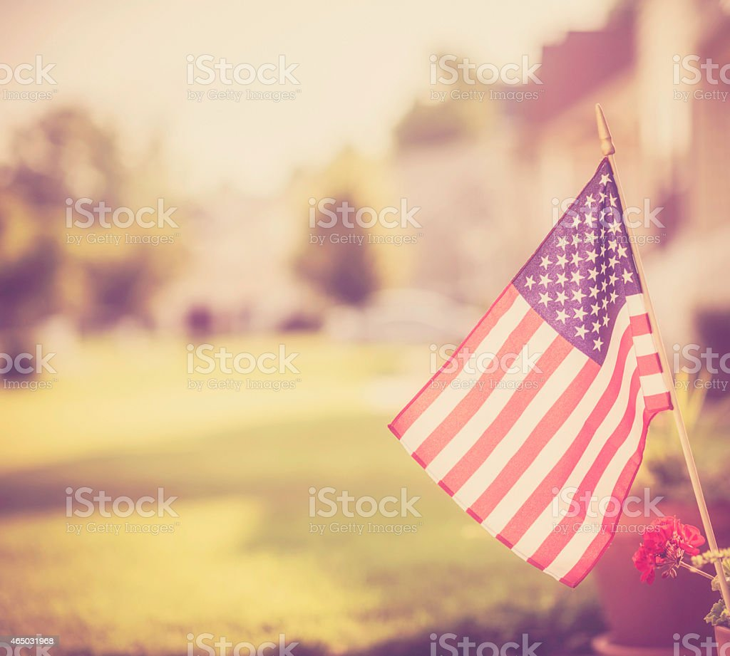 Patriotic American Homestead. Vintage toned waving flag for American holidays. stock photo