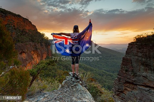 Patriotic woman holding Australian flag in Blue Mountains Australia.  Celebrate Australia Day, Sports supporter, tourism, Australian travel, Aussie Pride themes.  Selective focus to woman only.  Flag shows some motion from wind.
