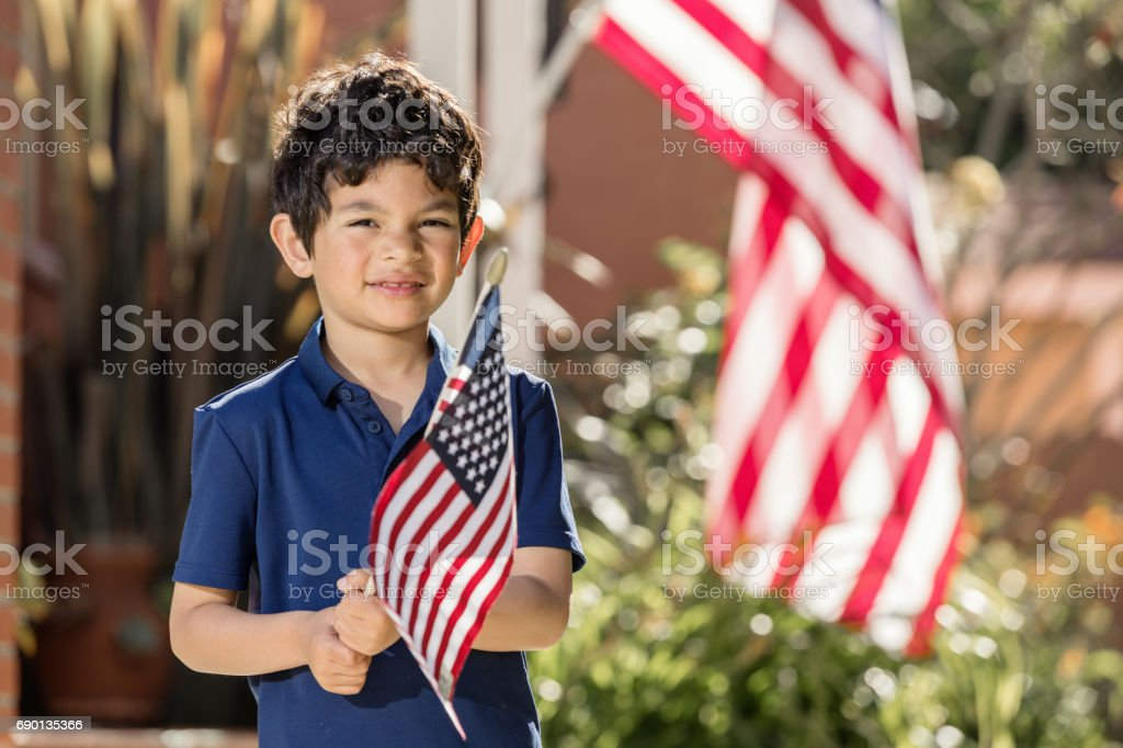 Patriotic Boy Holding an American Flag Outside his Home stock photo