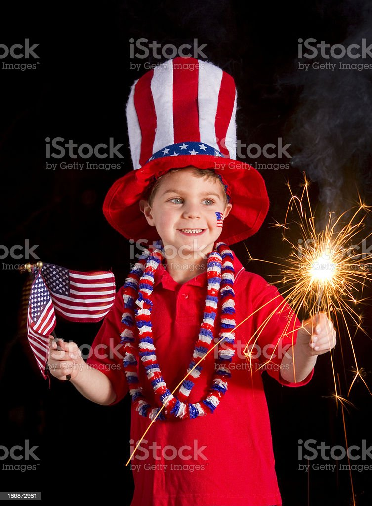 Patriotic Boy Holding Fourth Of July Sparkler & Flags stock photo