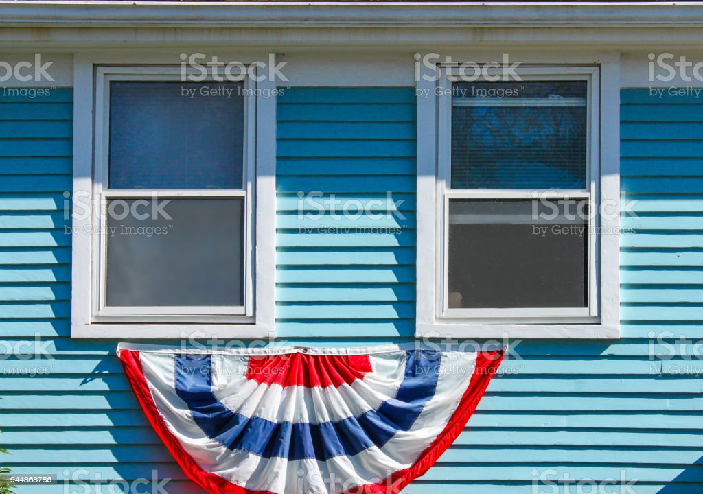 Patriotic bunting displayed beneath two wood window on a blue painte house for Memorial Day or the 4th of July USA stock photo