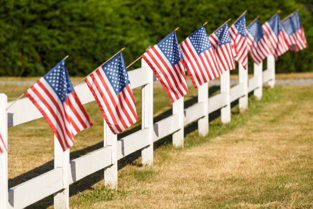 Patriotic display of American flags waving on white picket fence. Typical small town Americana Fourth of July Independence Day decorations. stock photo