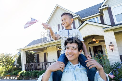 Cheerful mid adult Hispanic man carries his son on his shoulders. The boy is waving a small American flag.