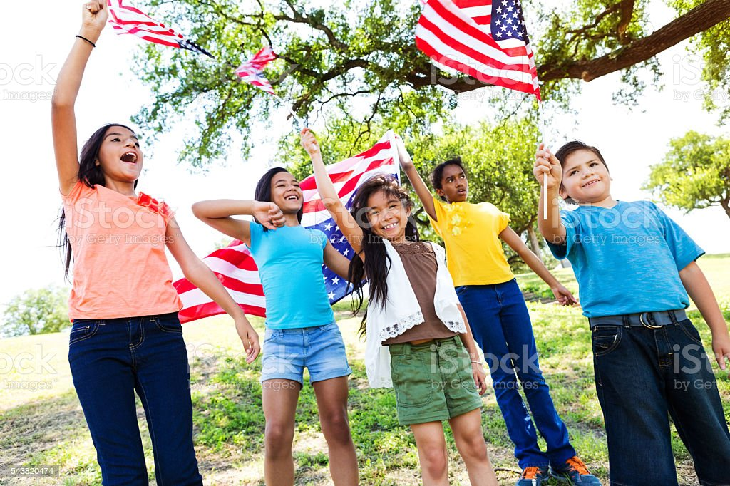 Patriotic friends wave flags at a parade stock photo