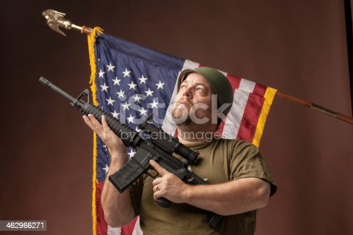 istock patriotic GI soldier raises rifle in front of USA flag 462966271