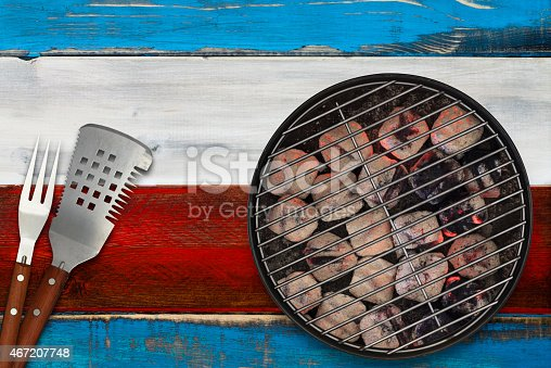 470765518istockphoto Patriotic Grill with Glowing Briquettes and BBQ Utensils 467207748