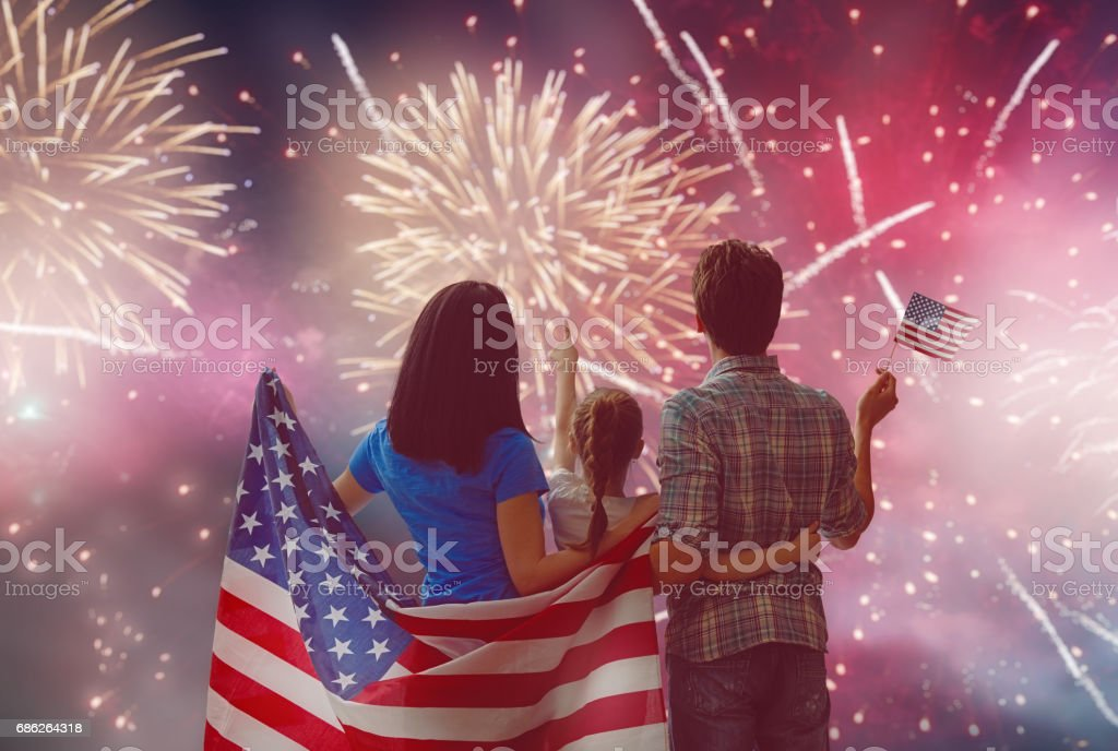 Patriotic holiday. Happy family Patriotic holiday. Happy family, parents and daughter child girl with American flag outdoors. USA celebrate 4th of July. Adult Stock Photo