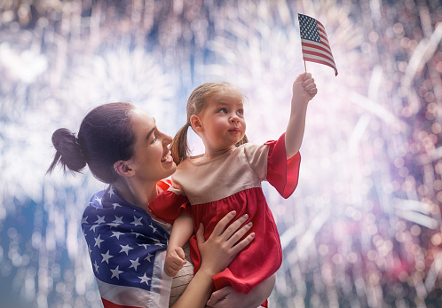 Patriotic holiday. Happy kid, cute little child girl and her mother with American flag. USA celebrate 4th of July.