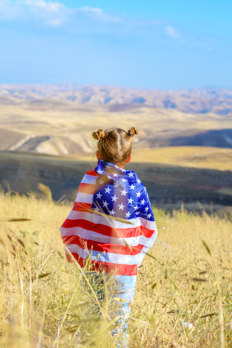 istock Patriotic holiday. Happy kid, cute little child girl with American flag. USA celebrate 4th of July. 1159353588