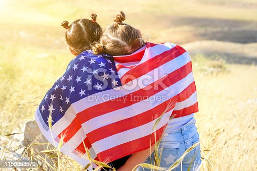 istock Patriotic holiday. Happy kids, cute little children girls with American flag. USA celebrate 4th of July. 1159353579