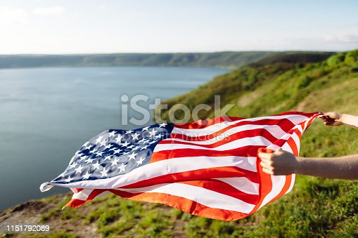 istock Patriotic holiday. Young woman holding USA flag. 1151792089
