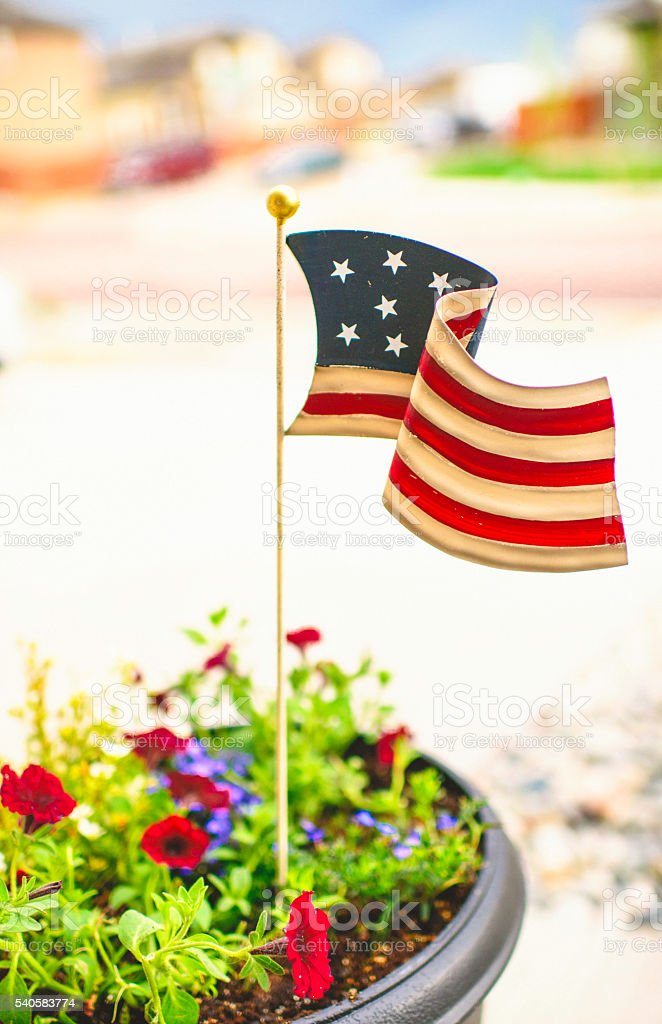 Patriotic Homestead. Small town America. US Flag in plant pot stock photo