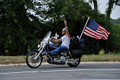Leesburg, Virginia, USA- August 19, 2011: Participant in 911 Tribute ride that takes place annually to honor the victims of the 911 attack of September 11, 2001. The procession begins in Shanksville, PA, then goes to the Pentagon in Virginia, and ends at Ground Zero, New York City. Here a participant rides through the outskirts of Leesburg, Virginia, on his way to the Pentagon. He is displaying a large American Flag and giving the Peace Sign with his left hand.