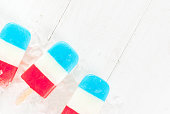ICe cream. Patriotic Red White Blue Popsicles for 4th of July holiday, on white wooden table. copy space top view