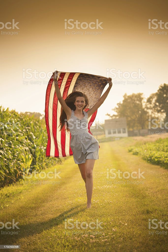 Patriotic Teen Farm Girl Running Through Field Waving US Flag stock photo