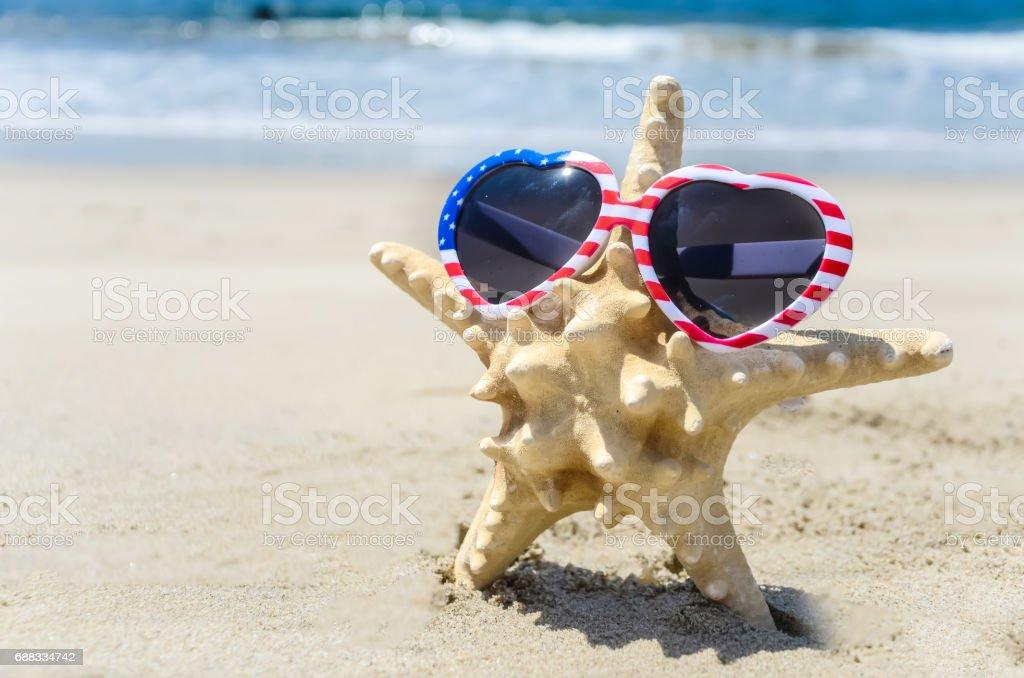 Patriotic USA background with starfish on the sandy beach stock photo