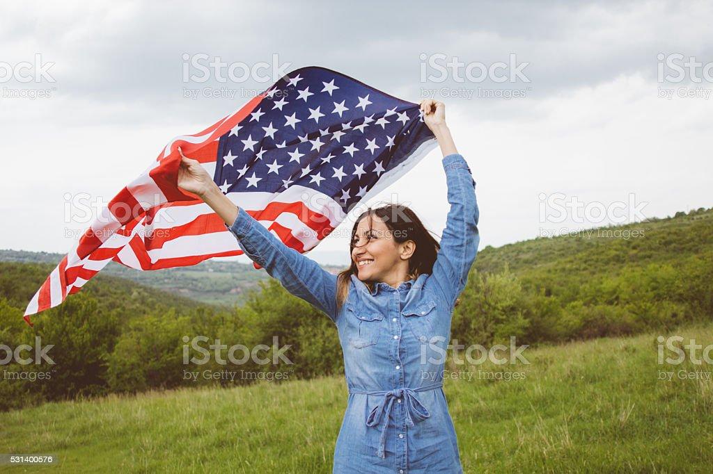 Mulher com O Patriota Bandeira americana realizado em fique de mãos - foto de acervo