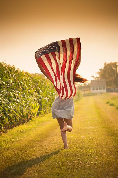 patriotische junge farm mädchen läuft über feld winken uns flagge - hofkleider stock-fotos und bilder