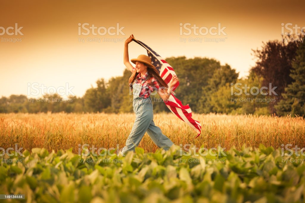 Patriotic Young Farm Girl Walking Through Field with US Flag stock photo