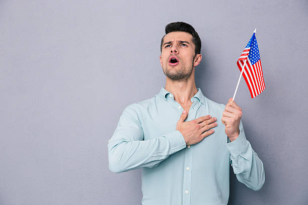 patriotic young man holding us flag - national anthem stock photos and pictures