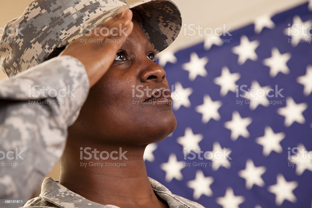 Patriotism: African descent military woman salutes American flag. stock photo