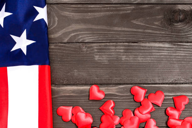 USA patriotism concept. Red hearts and USA flag on a wooden background.The view from the top stock photo