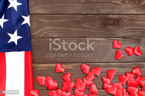 istock USA patriotism concept. Red hearts and USA flag on a wooden background.The view from the top. Celebration, love. 953830038