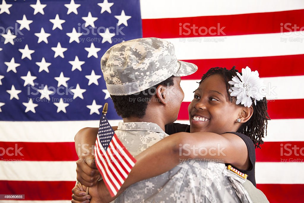Patriotism: Military mom being welcomed home by daughter. USA flag. royalty-free stock photo