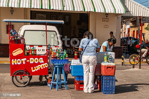 Leon, Nicaragua - November 27, 2008: Patron in front of red Hot-dog and drinks push cart with vendor present and many bottles on display in front of El Sestea bar and restaurant.