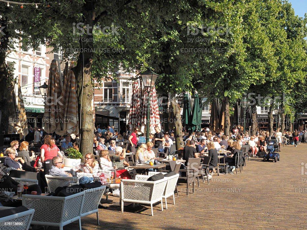 Patrons frequenting cafes at the historic city square stock photo
