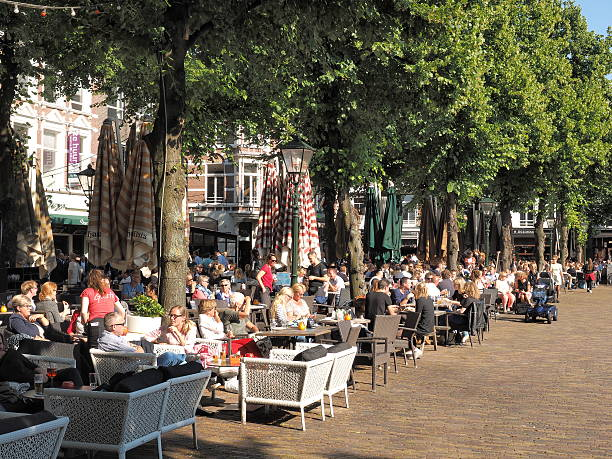 patrons frequenting cafes at the historic city square - den haag stockfoto's en -beelden