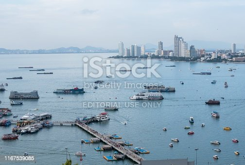 Tourists throng a pier in the foreground in Pattaya to travel on ferries to nearby islands in Thailand. Pattaya is a popular destination for both locals and tourists.
