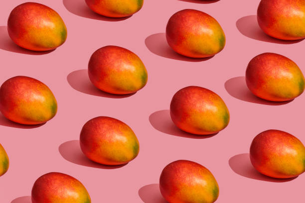 pattern composition of a sweet tasty mango lying next to a pink background , top view - ripe stock photos and pictures