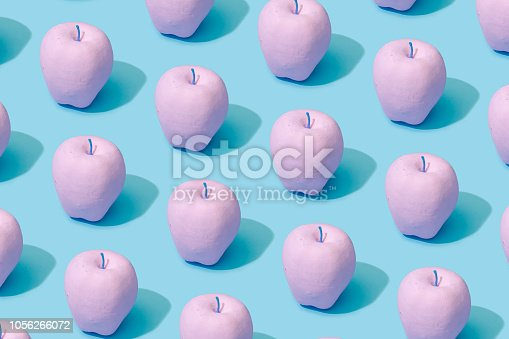 istock Pattern composition of pink painted apples on pastel blue background. 1056266072