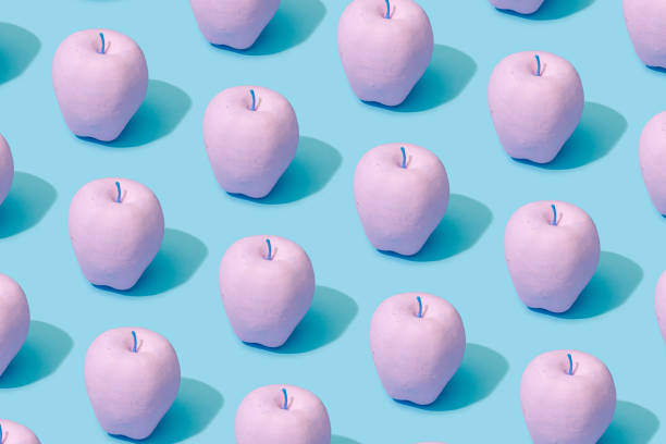 Pattern composition of pink painted apples on pastel blue background. stock photo