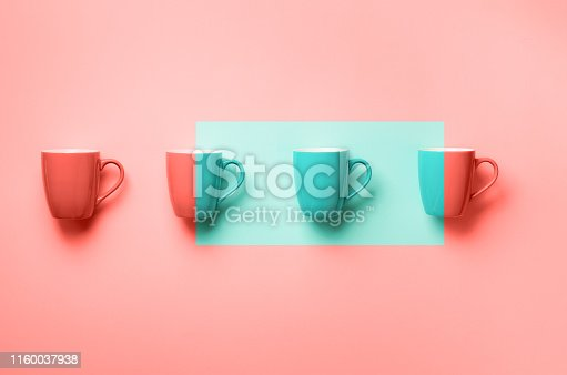 istock Pattern from pink cups over trendy coral color background. Birthday party celebration, baby shower concept. Pastel colors. Banner. Minimalist style design 1160037938