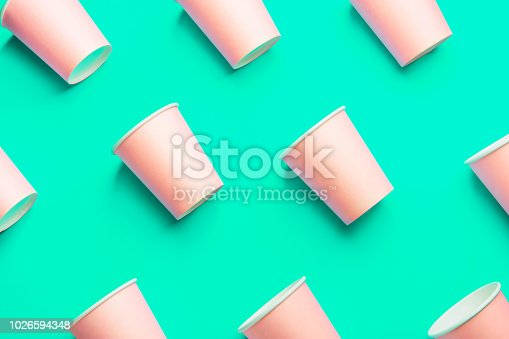 istock Pattern from Pink Paper Drinking Cups Arranged Diagonally on Light Green Turquoise Backgrounds. Birthday Party Celebration Abstract Fashion Baby Shower Concept. Pastel Colors. Minimalist Style 1026594348