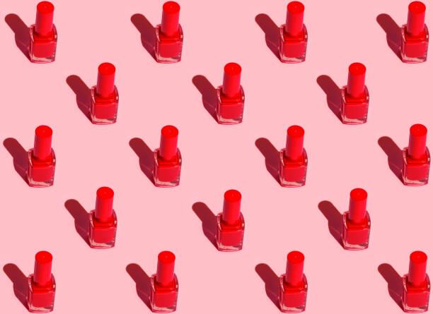 Muster aus roten Nagellackflaschen, die in symmetrischen geometrischen Reihen auf fuchsias rosa Hintergrund angeordnet sind. Pop-Art-Stil mit starken Sonnenlicht-Schatten. Mode machen Kosmetik-Beauty-Konzept – Foto