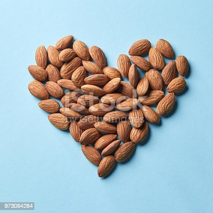 Dried almonds in the shape of heart on a blue paper background flat lay. Organic food