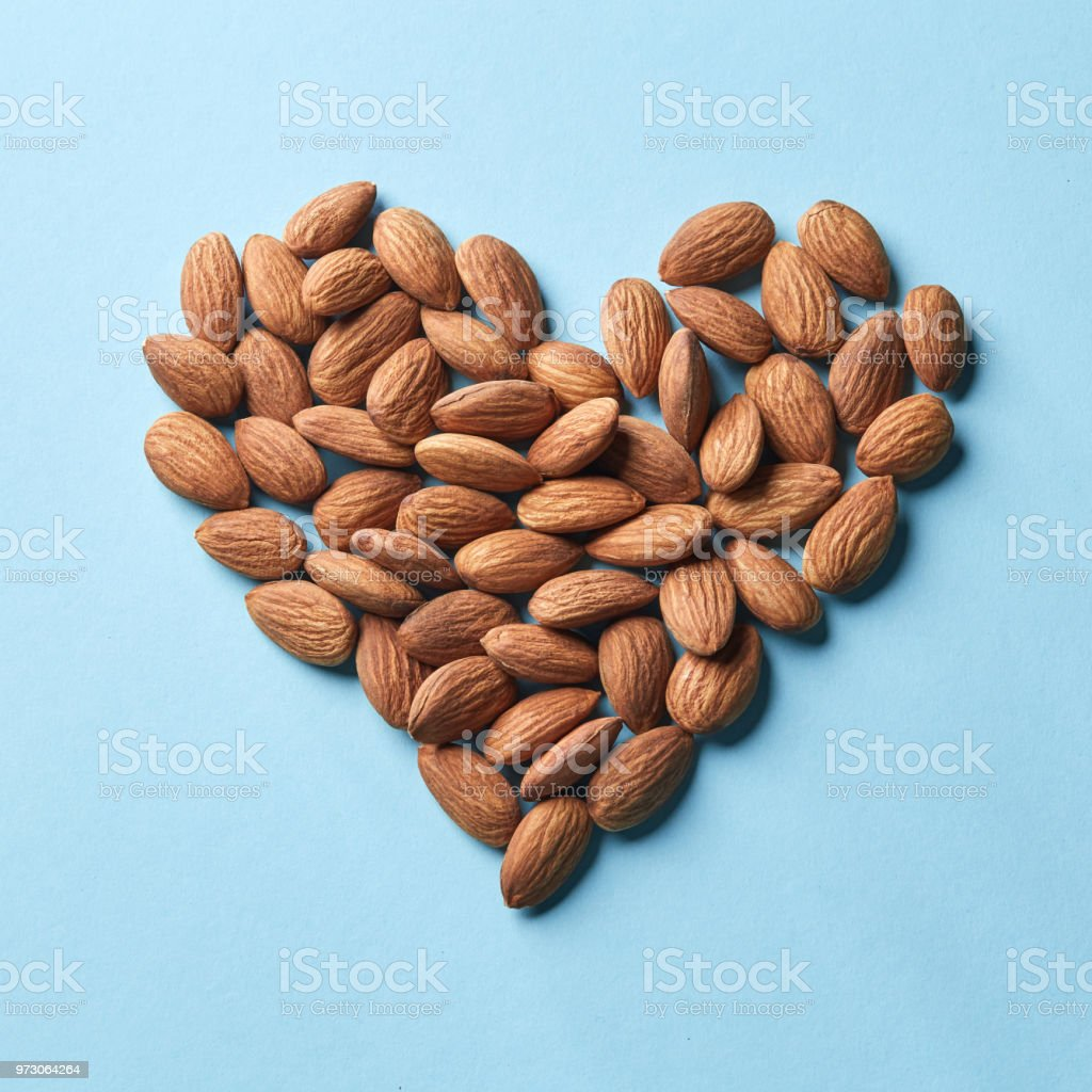 Pattern in the form of heart from almonds on a blue paper background stock photo