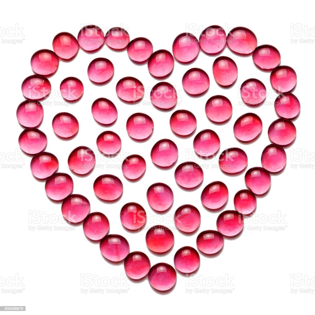 Pattern in the form of heart from red translucent glass beads. Isolated on white. stock photo