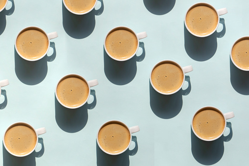 Pattern made of cup of cappuccino on blue background