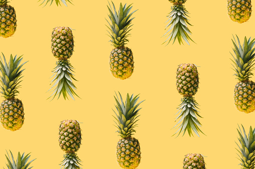 Pattern made of many modern, creative fresh exotic funky pineapples against illuminated yellow background. Levitating natural organic ananas summery concept.