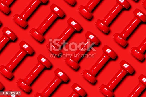 istock Pattern made of red dumbbells on red background. 1163885617