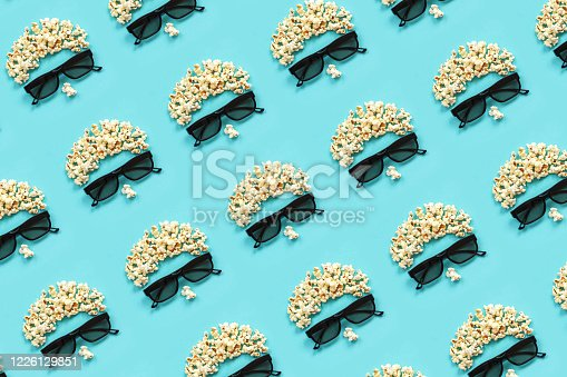956942702 istock photo Pattern made with abstract image of viewer, 3D glasses and popcorn on blue background. Creative concept cinema movie and entertainment Flat lay Top view 1226129851