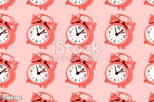 istock Pattern made with alarm clock on coral background. 1155351568