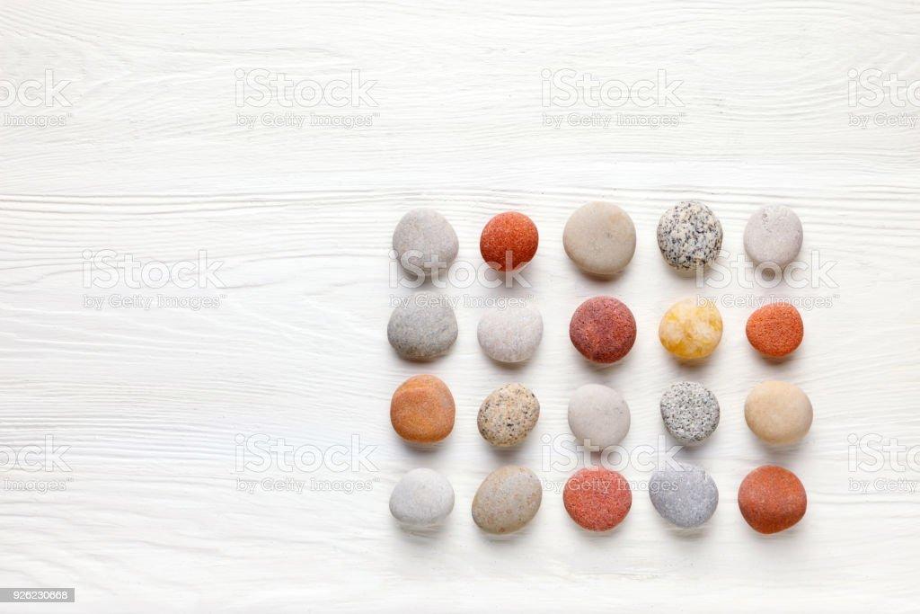 Muster aus farbigen Kieselsteinen auf weißem Hintergrund aus Holz. Flach legen, Top Aussicht – Foto